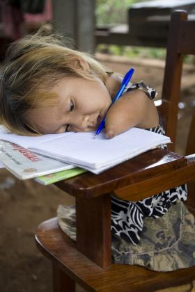 Girl writing at school, Cambodia