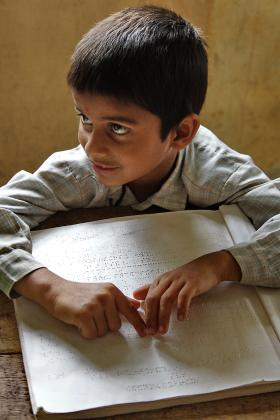Young boy reading braille